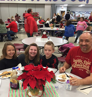 Young girl in black shirt, woman in black shirt, boy in black shirt and man in red shirt eating at a table with a poinsettia centerpiece