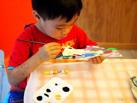 Preschool boy painting paper plate bird craft