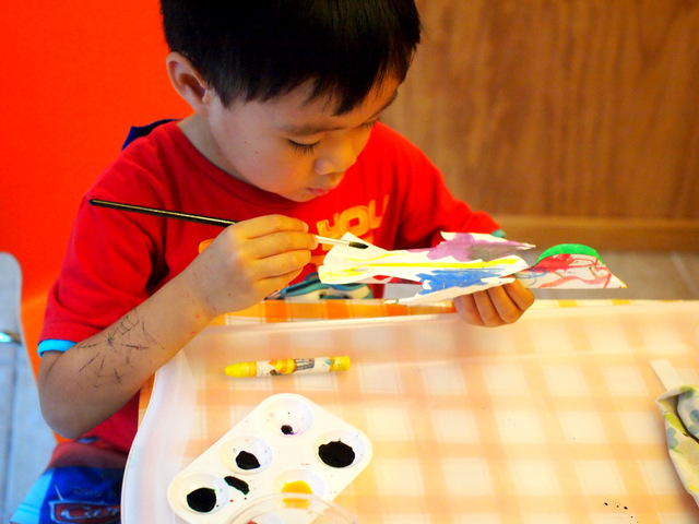 Preschool boy painting paper plate bird craft