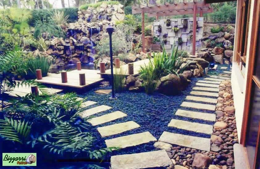 Caminhos com pedra rústica no jardim com o lago de carpas, a ponte de madeira que leva até o pergolado de madeira. Casa em condomínio em Atibaia-SP.