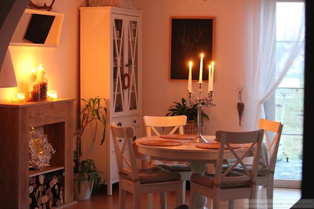 salon, drewniana ściana w salonie, biały stół, białe krzesła, lustro w ramie okiennej, świece, świecznik, szara sypialnia, atrapa kominka DIY,