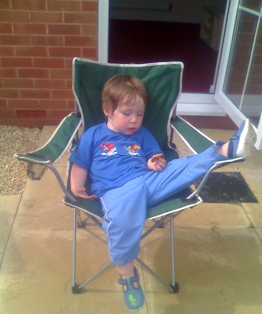Toddler Sleeping Slumped in a Lawn Chair. Clutching a Cookie