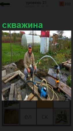 На дачном участке мужчина выкачивает из скважины воду насосом