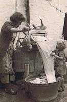 Woman using crank washer and child helping feed sheets into a wash tub