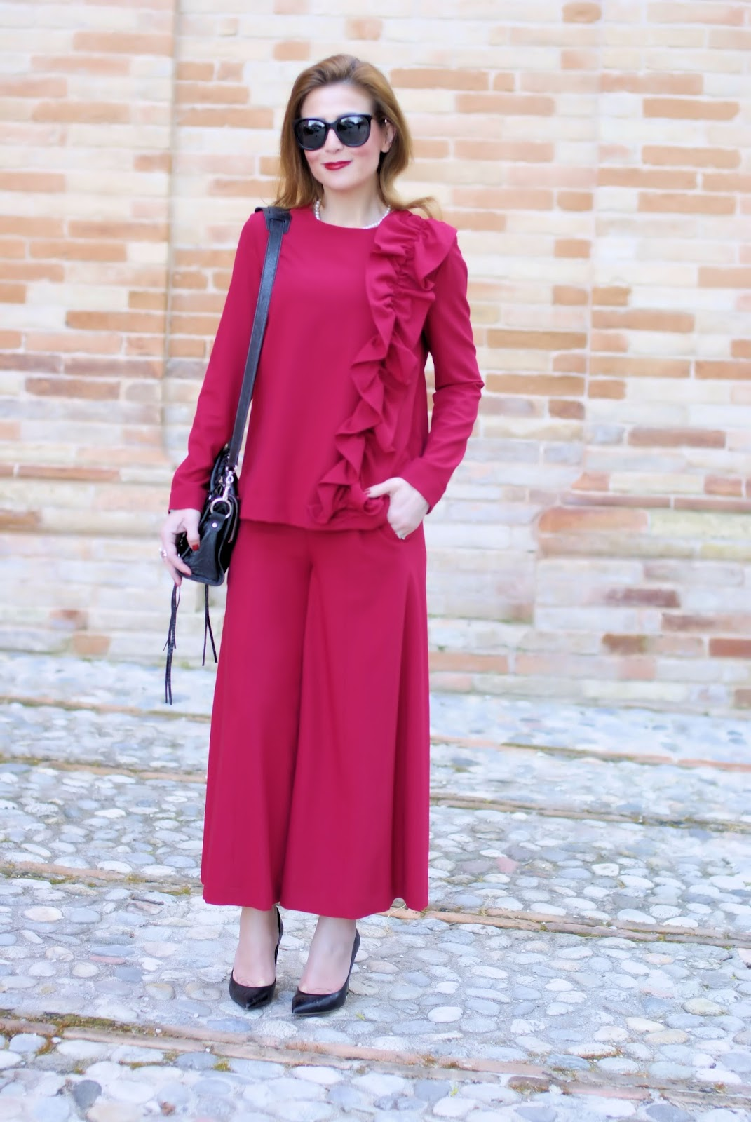 Woman in red with a ruffled blouse and wide leg cropped pants on Fashion and Cookies fashion blog, fashion blogger style