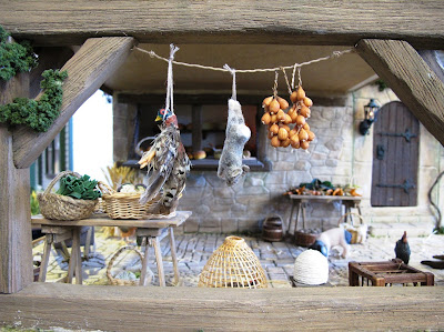 Medieval market hall with game and onions hung from the ceiling, and tables of produce under.