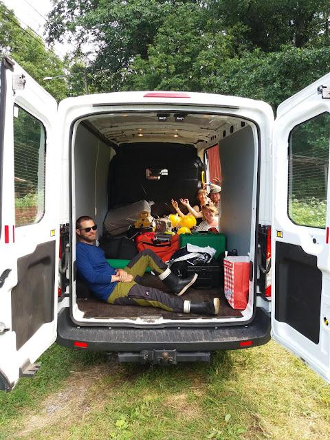 Pakettiauto pakattu, yksi istuu poikittain sisällä, kolme muuta katsovat sivuovesta sisään.