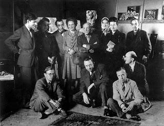 fotografía en conjunto de Sarte y Camus sentados en el suelo junto a otros intelectuales de la época como Beavouir o Piccaso