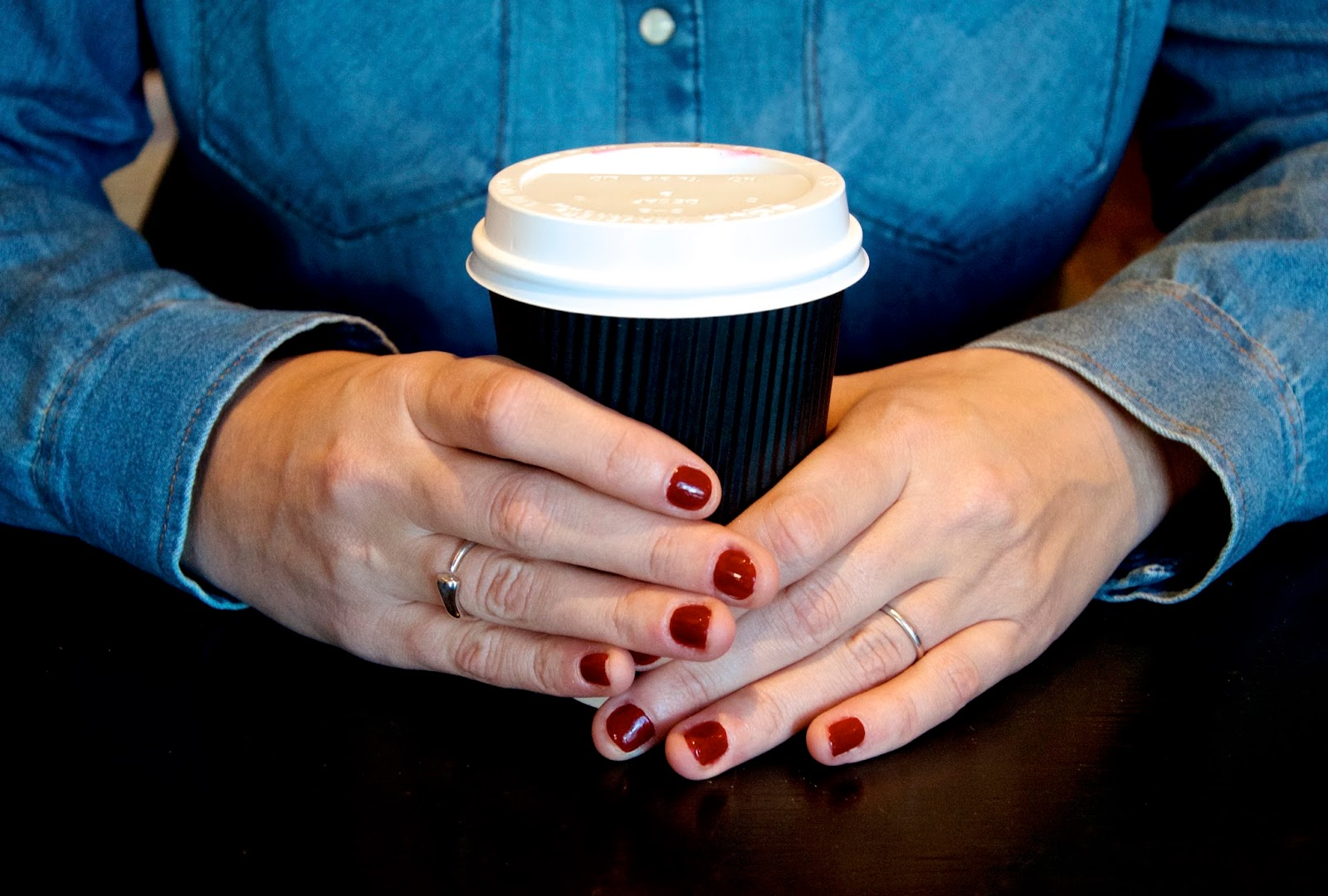 Coffee, red nails and denim shirt