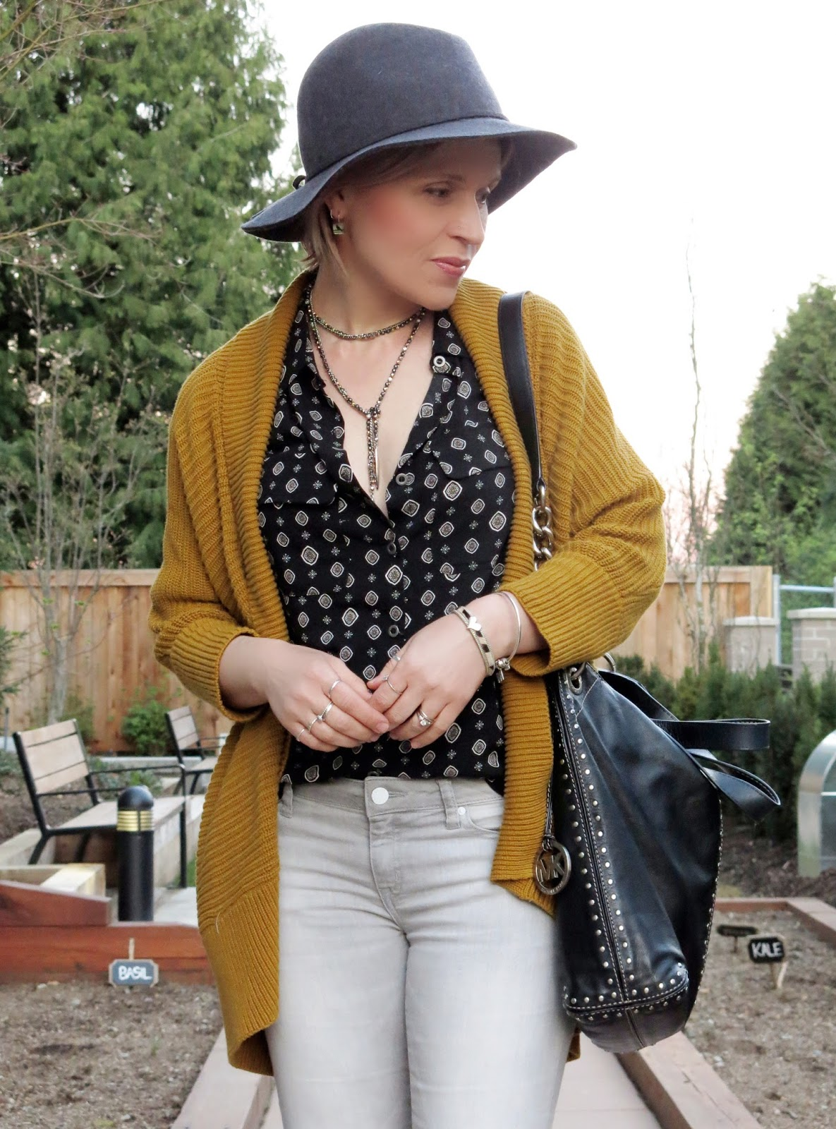 black patterned shirt, grey skinny jeans, drapey mustard cardigan, floppy hat, MK bag