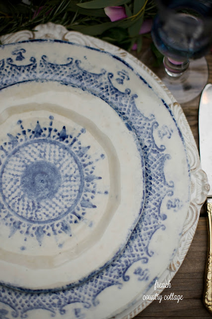 Blue and white hand painted dishes on carved chargers table setting