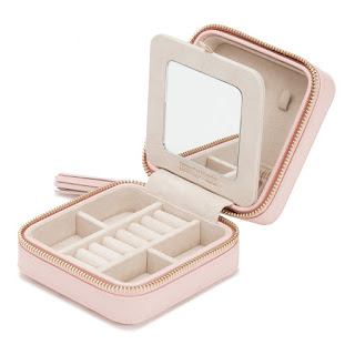 A small rose quartz leather box with a zip around the middle, places to store jewellery and a mirror