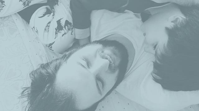 Foto de pai e filho, deitados abraçados.