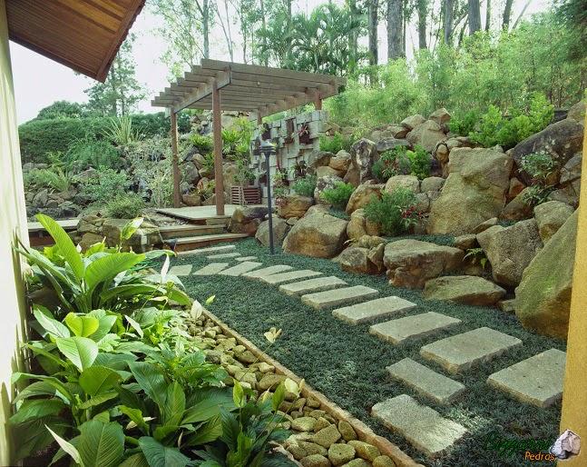 Caminho com pedra no jardim, muro de pedra artesanal com o pergolado de madeira e a canaleta com pedra moledo para captar a água da chuva.
