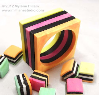 Stack of square black and pastel coloured bangles amongst a group of scattered licorice allsorts.