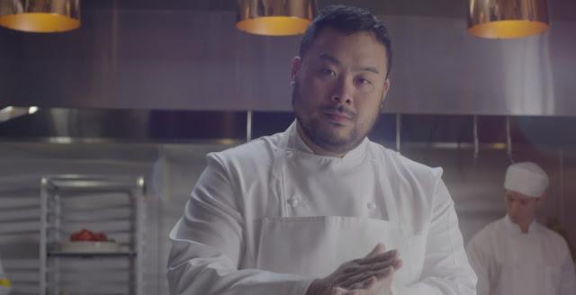 El chef David Chang vestido con traje de cocinero blanco impoluto en una cocina