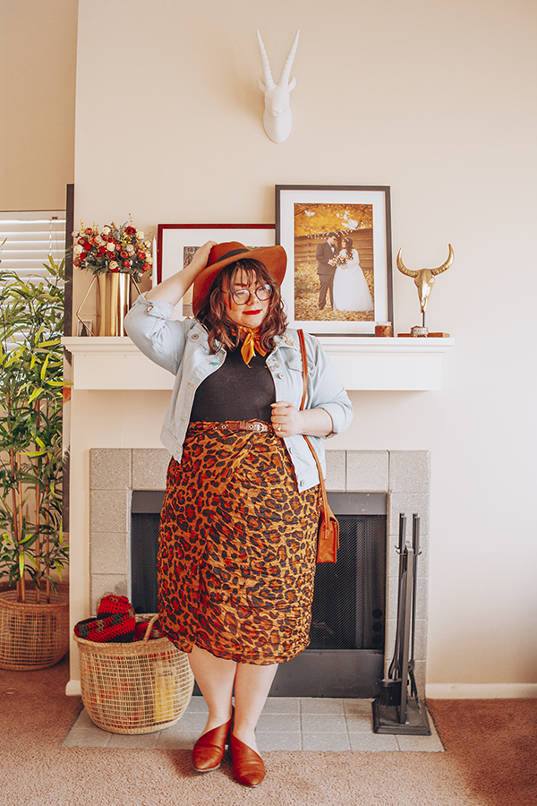 A Spring outfit of a camel brown panama hat, light wash denim jacket, black mockneck top, brown leopard skirt and brown d'orsay flats.