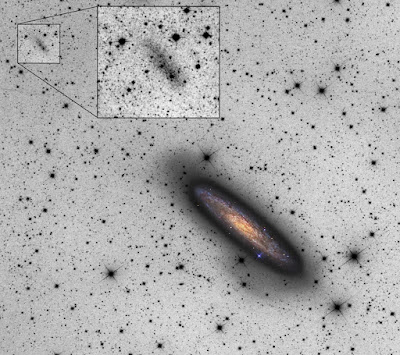 Astronomers spot a faint dwarf galaxy disrupting a nearby giant spiral galaxy