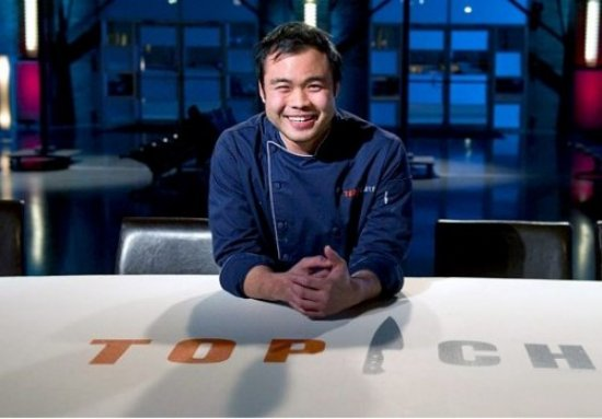 Top Chef - Paul Qui smiles as he leans against the judges table