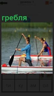 Двое спортсменов на каноэ занимаются греблей на водном канале, соревнуясь друг сдругом