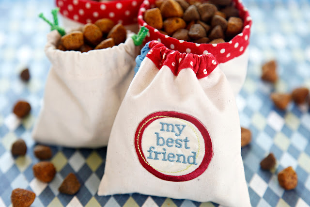 Homemade drawstring dog treat bags on a table with treats
