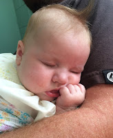 a child sleeping in her father's arms