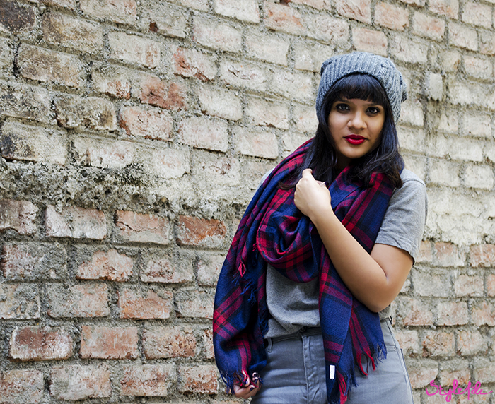 Image of a woman against a brick wall wearing shades of grey with a beanie cap, red lips and a plaid scarf for a fashion outfit post