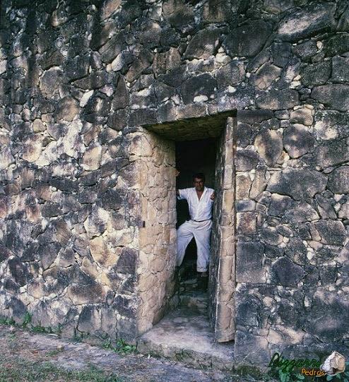 Detalhe do muro de pedra com a porta de pedra e um túnel com pedra moledo que leva até a residência.