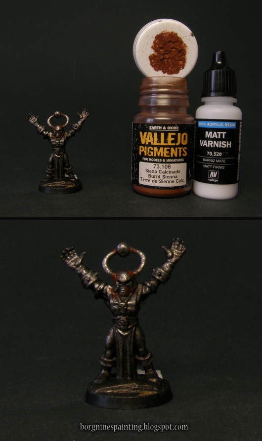 Photo showing the first step of applying the pigment, with a small amount of it concentrated around the base of the miniature's horns - with a pot of Vallejo Burnt Sienna pigment and Vallejo Matt Varnish visible on the right.