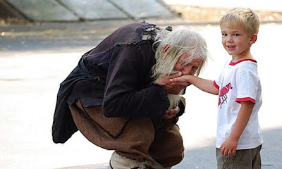 Un mendigo le besa la mano a un niño por amistad