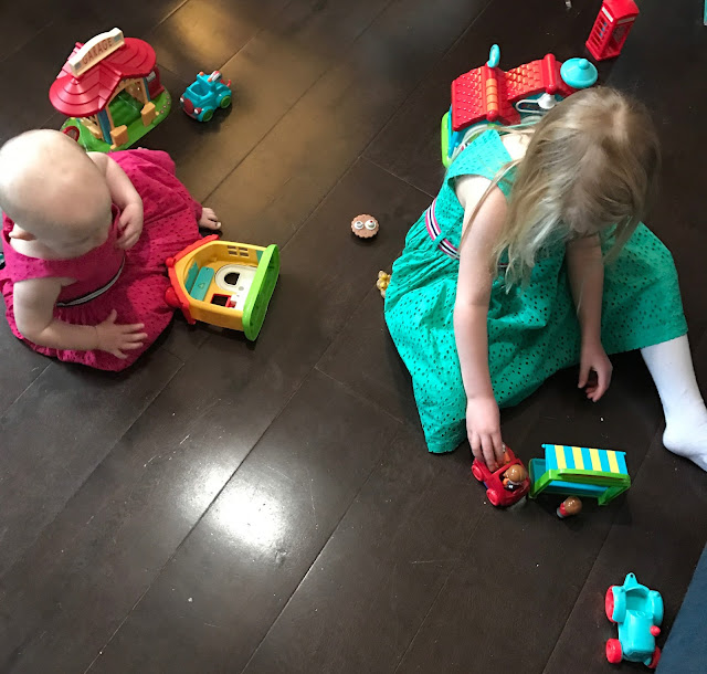 A baby girl in a pink dress and a 5 year old girl in a green dress sitting on a brown wooden floor playing with toys including a number of plastic houses