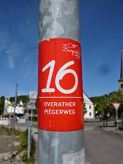 """An einer Laterne klebt ein roter Aufkleber mit einer weißen 16 und der Aufschrift """"Overather Pilgerweg"""""""