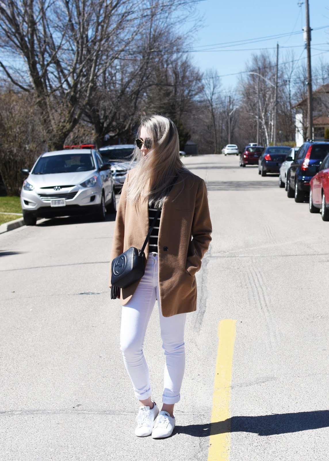 OOTD with camel Zara coat, white jeans, Gucci bag, and Adidas sneakers