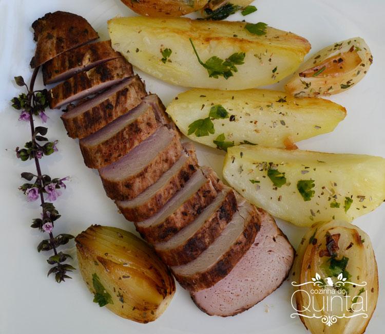 Filé mignon de porco assado com batatas, cebolas e ervas frescas na Cozinha do Quintal