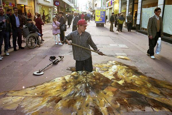 Kaldırımda büyük bir kuyu açan bir adamı gösteren kaldırım sanatı resmi