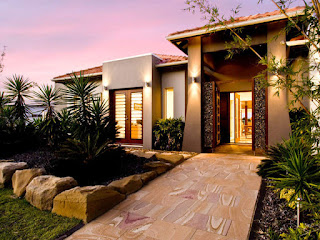 Single storey house facades with stones and planters