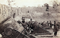 Historic photograph of soldiers standing beside mortar guns