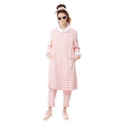 A girl wearing a pink checked coat and trousers.