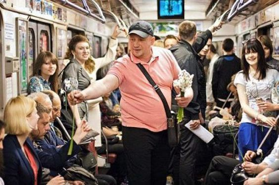 12 Powerful Images That Prove There's Still Kindness In The World - This man is offering flowers to every woman on the subway.
