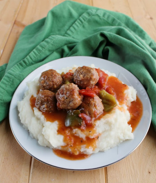 plate of mashed potatoes and swiss meatballs with green napkin