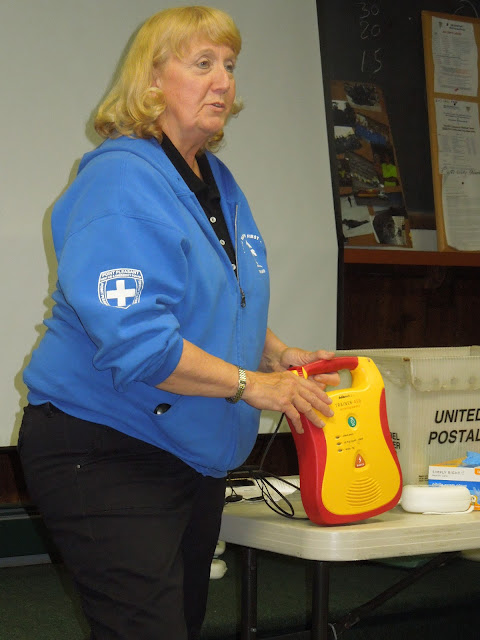Flo Melo provides instruction on the operation of a training AED unit