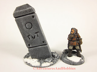 Tall stone pillar 25-28mm scale scenery piece with Frostgrave explorer - front view.