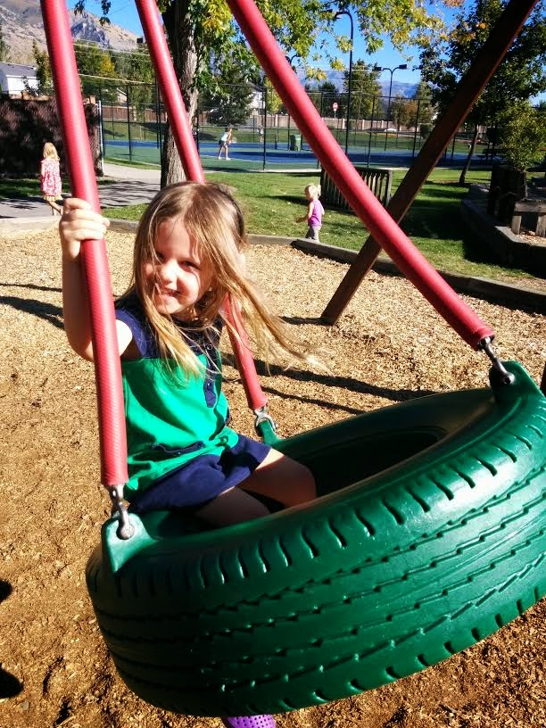 Toddler girl sitting in a tire swing at a park while laughing