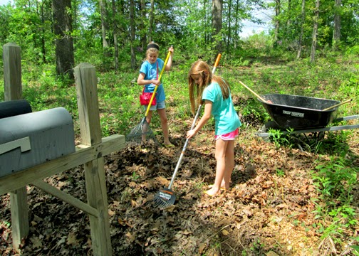 After Tessa's dad helped clear away weeds, the girls raked leaves to prepare a clean spot to plant their bulbs.