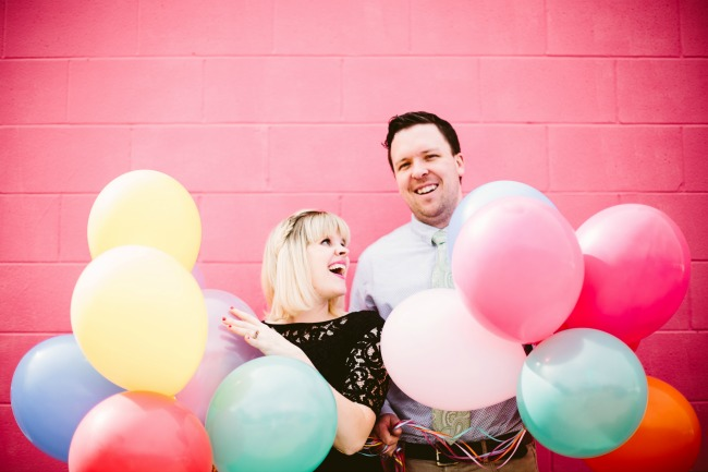 couples maternity photo shoot with balloons and pink wall