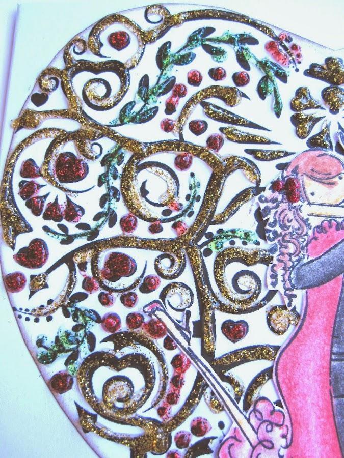 detalle de tarjeta de scrapbooking para San Valentín con corazón de filigrana decorado con glitter glue rojo, verde y amarillo