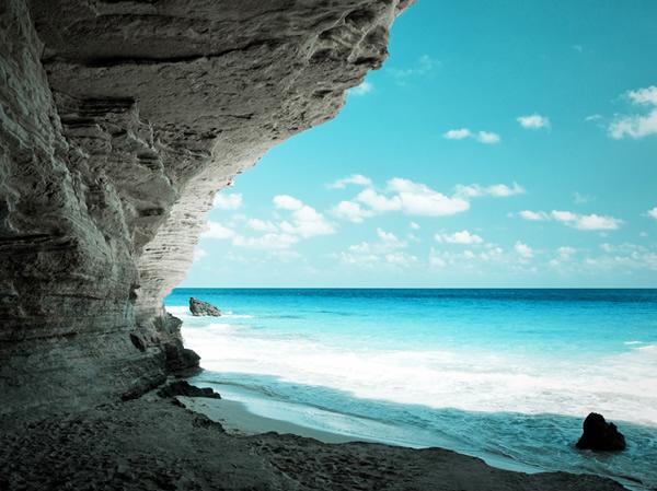 صورة للبحر وزرقة المياه من داخل كهف على الشاطئ