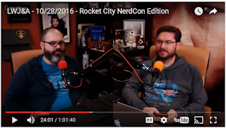 Two guys in a podcast studio. Semi-cute nerd types who probably bathe. They are wearing Bald Move t-shirts. One has a beard; both have glasses.