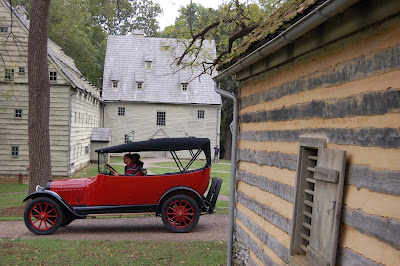Red pre-1915 auto at Ephrata Cloister with meetinghouse in background