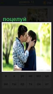 мужчина целует девушку держа её голову в своих руках